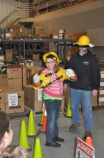 A Girl Scout tries on the safety gear First Electric linemen use in the field.