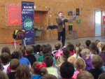 Magician Scott Davis teaches elementary students how to stay safe while using electricity.
