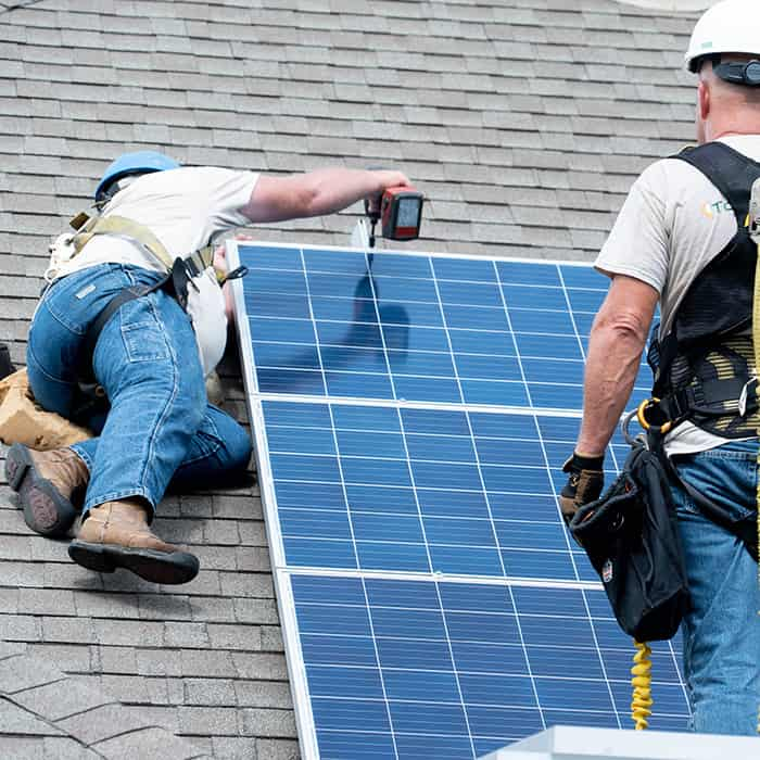 Solar panel installers on roof